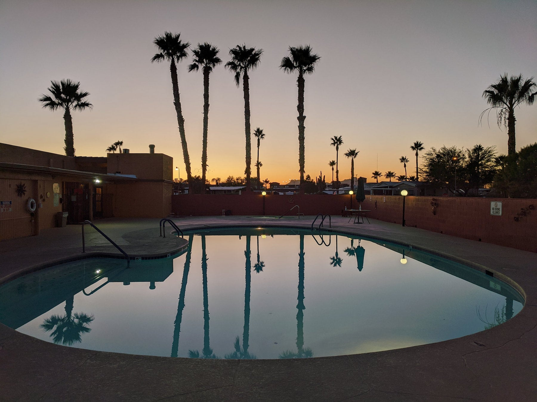 Sunset at a campground pool with tropical palm trees beside it.