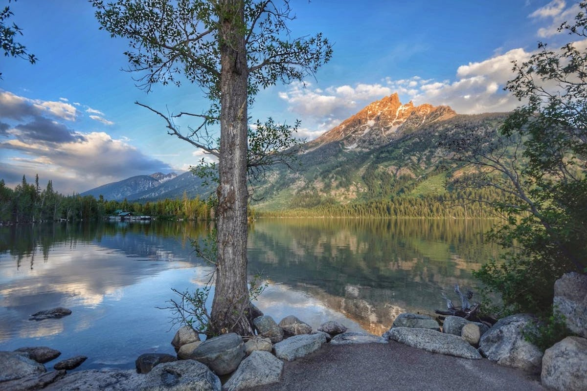 View from a campsite on along the edge of Jenny Lake below a snow dotted mountain.