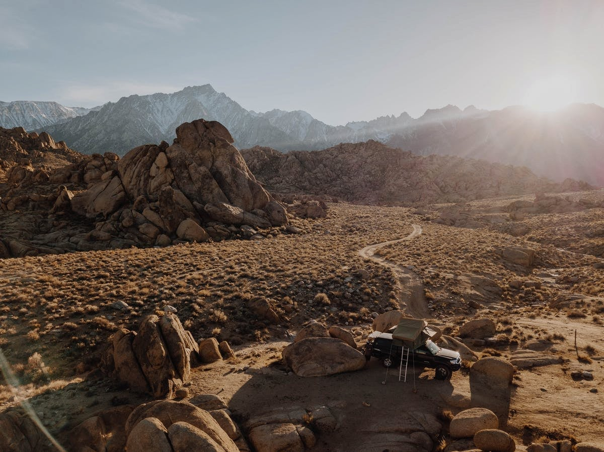 Rooftop tent on a truck parked during golden hour in the Alabama Hills with the snow capped Sierras in the background.