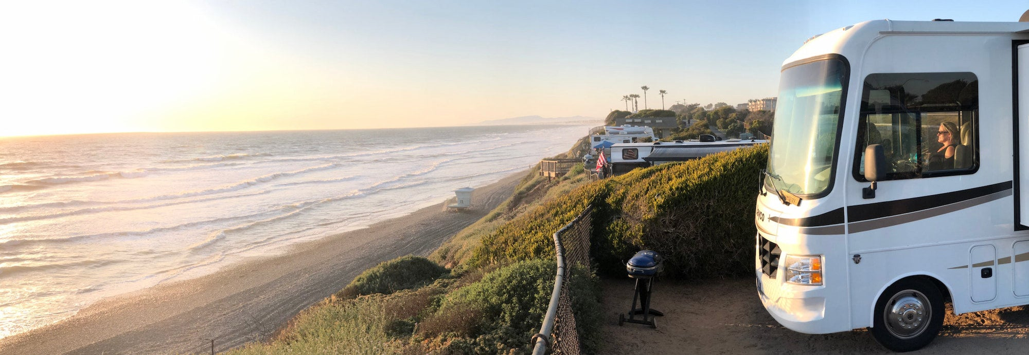 RV parked on edge of cliff overlooking the beach.