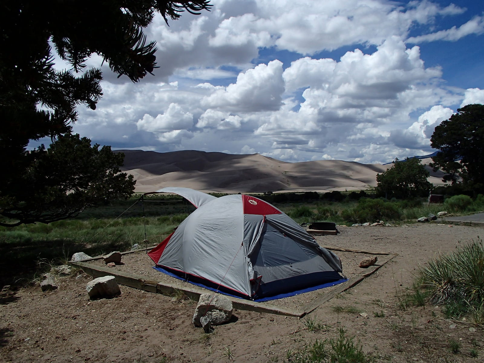 Tent at platform in foreground with rippled dunes of Great Sand Dunes National Park in Colorado in the background.