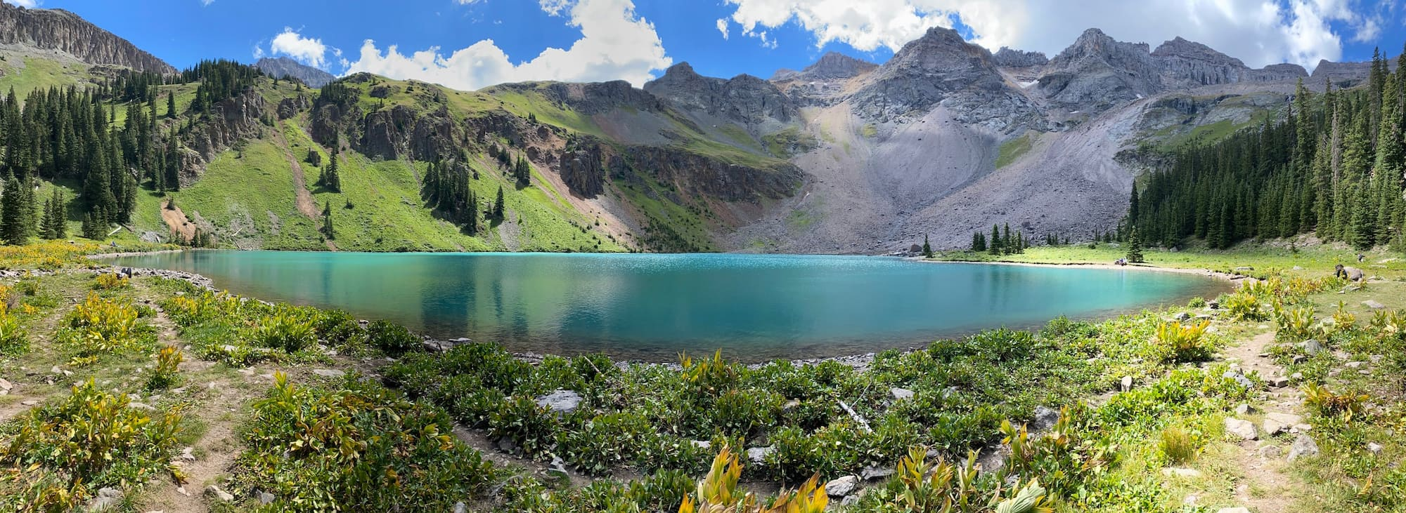 Turquoise alpine lake surrounded by a large mountain.