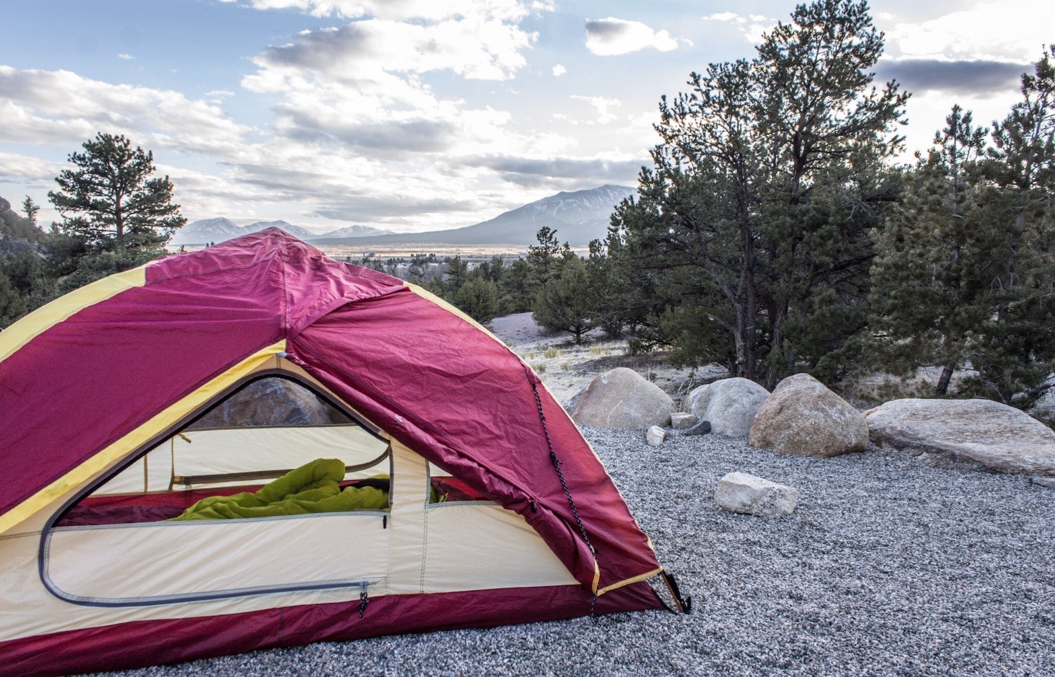 Red tent with sleeping bag inside set up in campsite beside evergreen trees and below large mountains in Colorado.