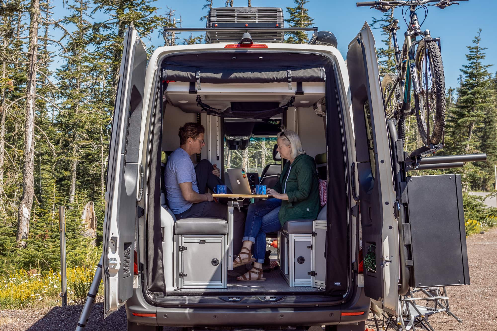 The Dyrt founders Kevin Long and Sarah Smith working remotely from their camper van.