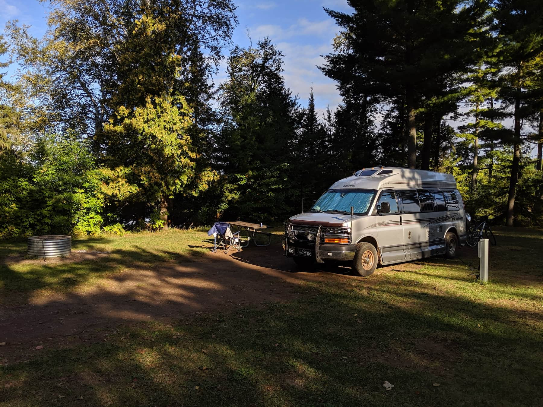 Van parked at campsite beside fire ring within the forest.