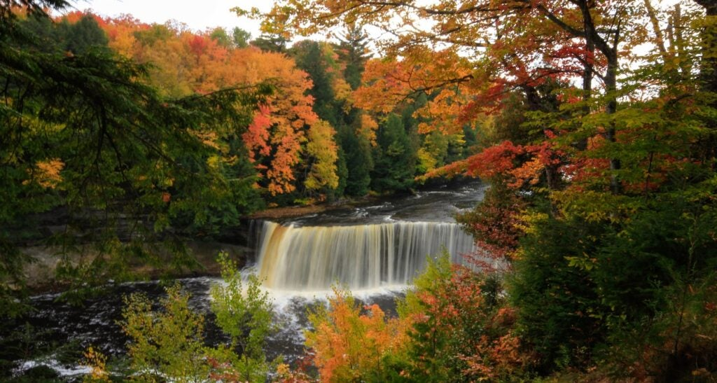 Cascading waterfalls surrounded by red and orange leaves of the fall foliage.