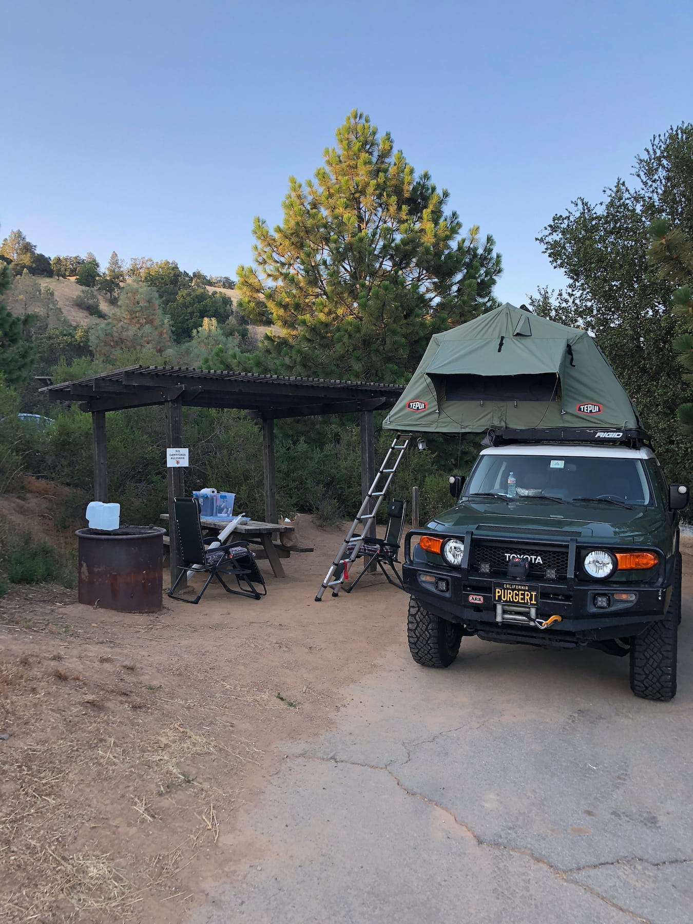 SUV with rooftop tent set up at a sandy forested campsite.
