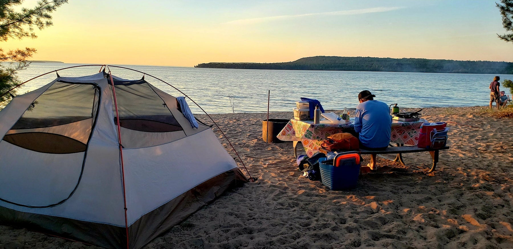 Camper sitting at beach campsite on a picnic table beside their tent during sunset.