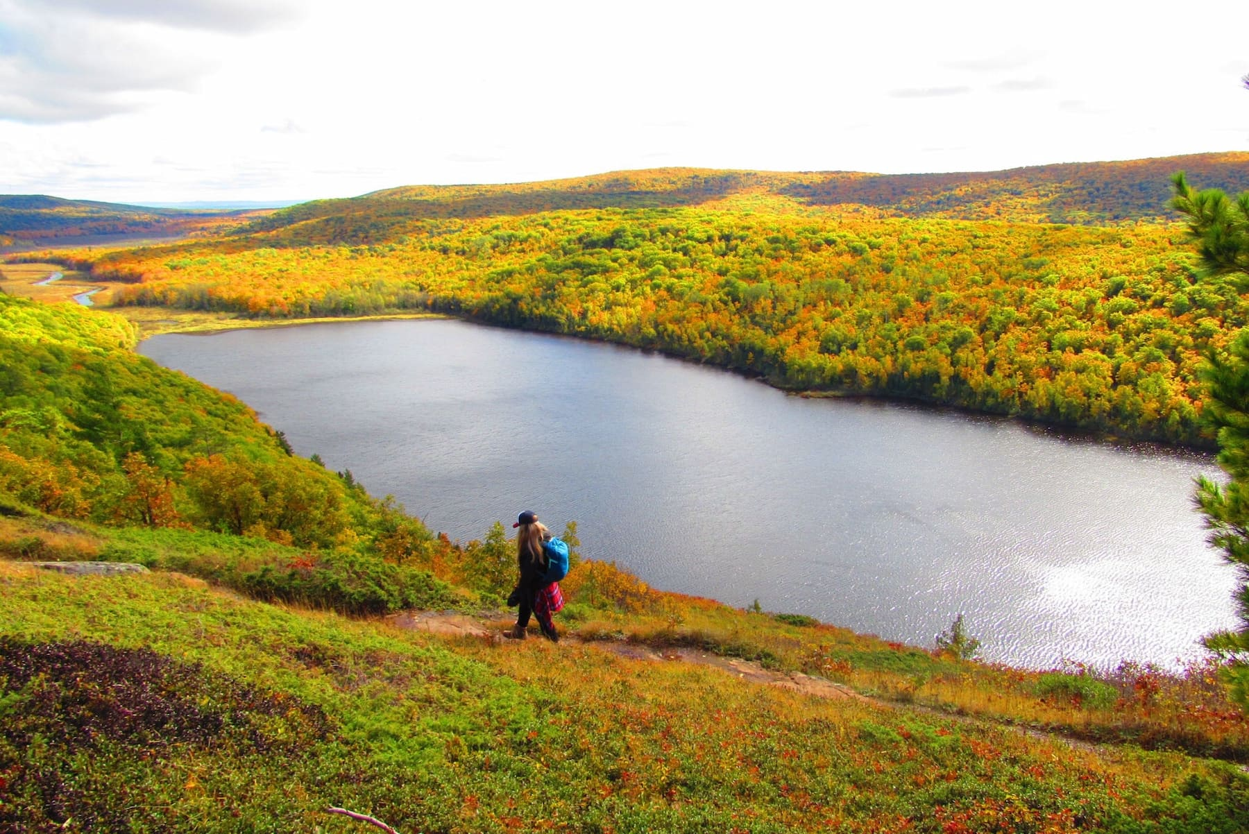 Woman hiking in the rolling hills of the Porcupine Mountains.
