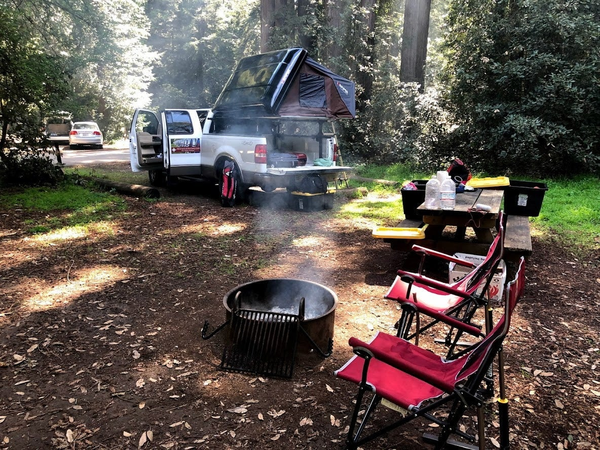 Campsite with pick up truck and smoking fire pit beside two camp chairs.
