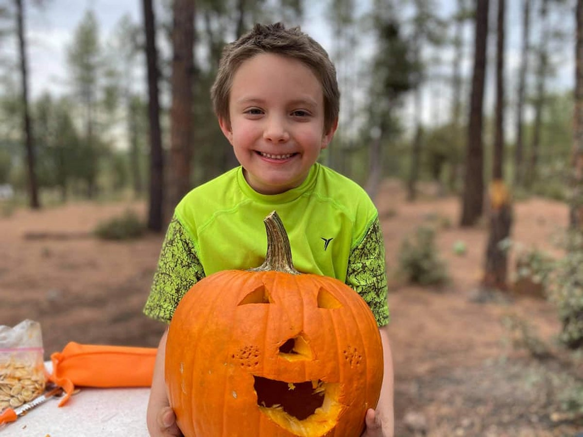 Camper celebrating halloween with a pumpkin carving at the campsite.
