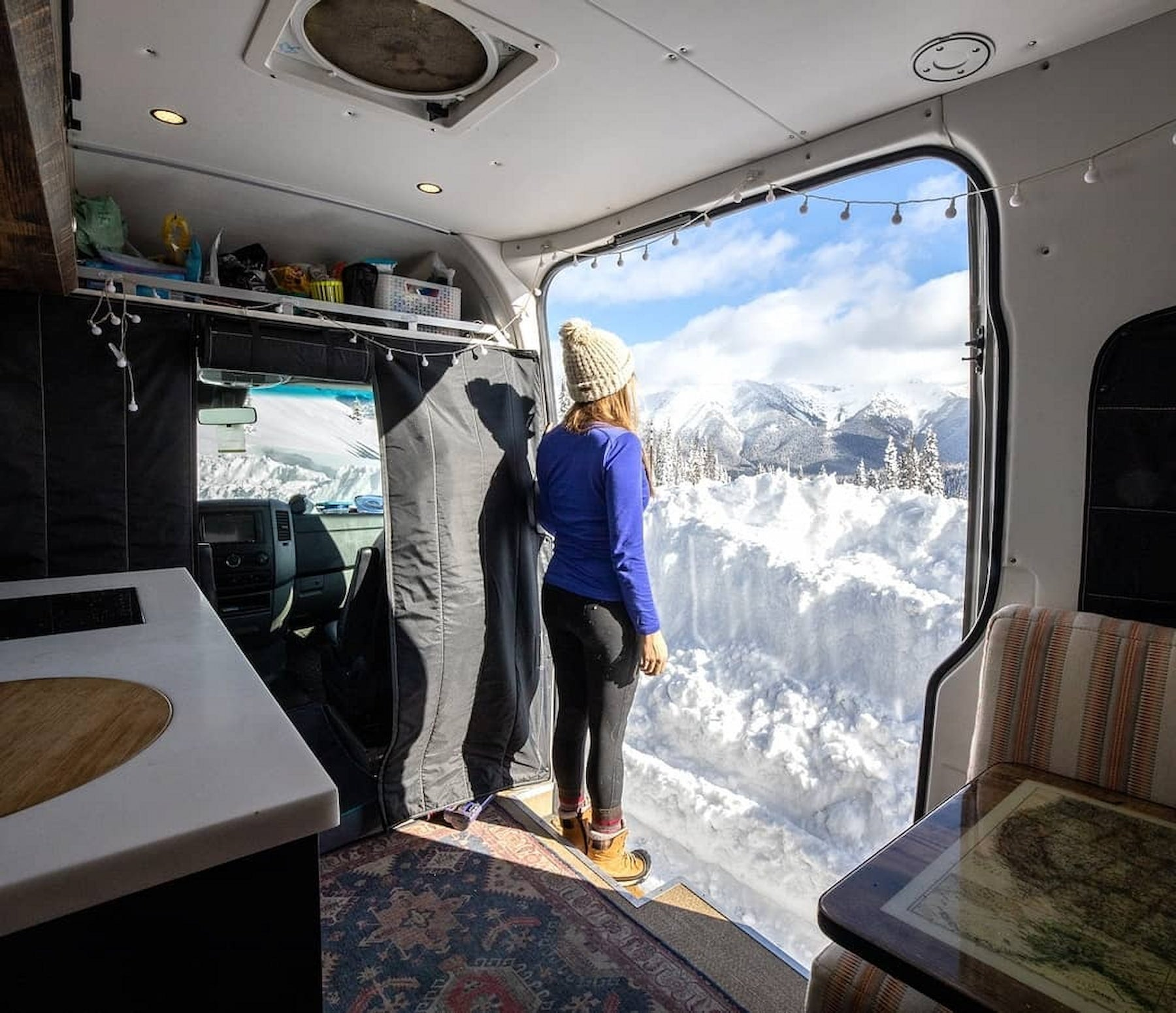 Kristin standing in the doorway of her van looking over the snow dusted mountains.