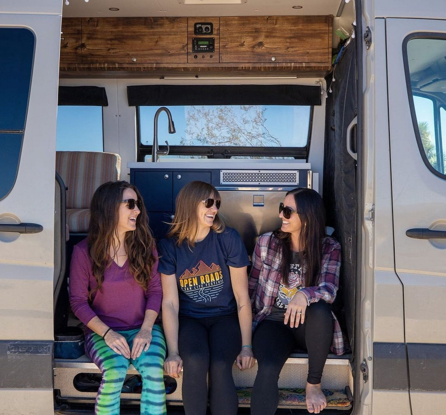 Group of women hanging out in a camper van.