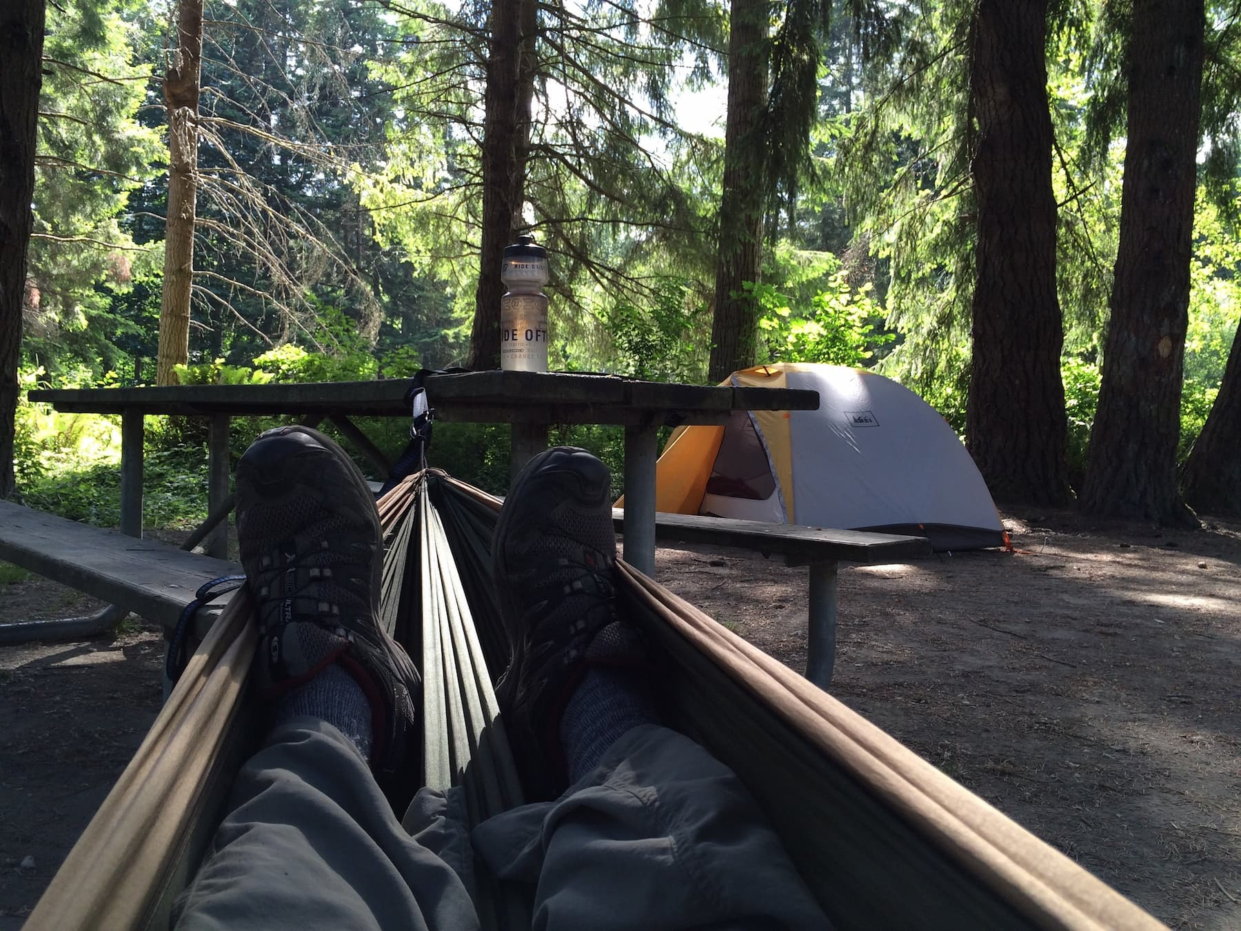 Point of view image from hammock at campsite with picnic table and orange tent.
