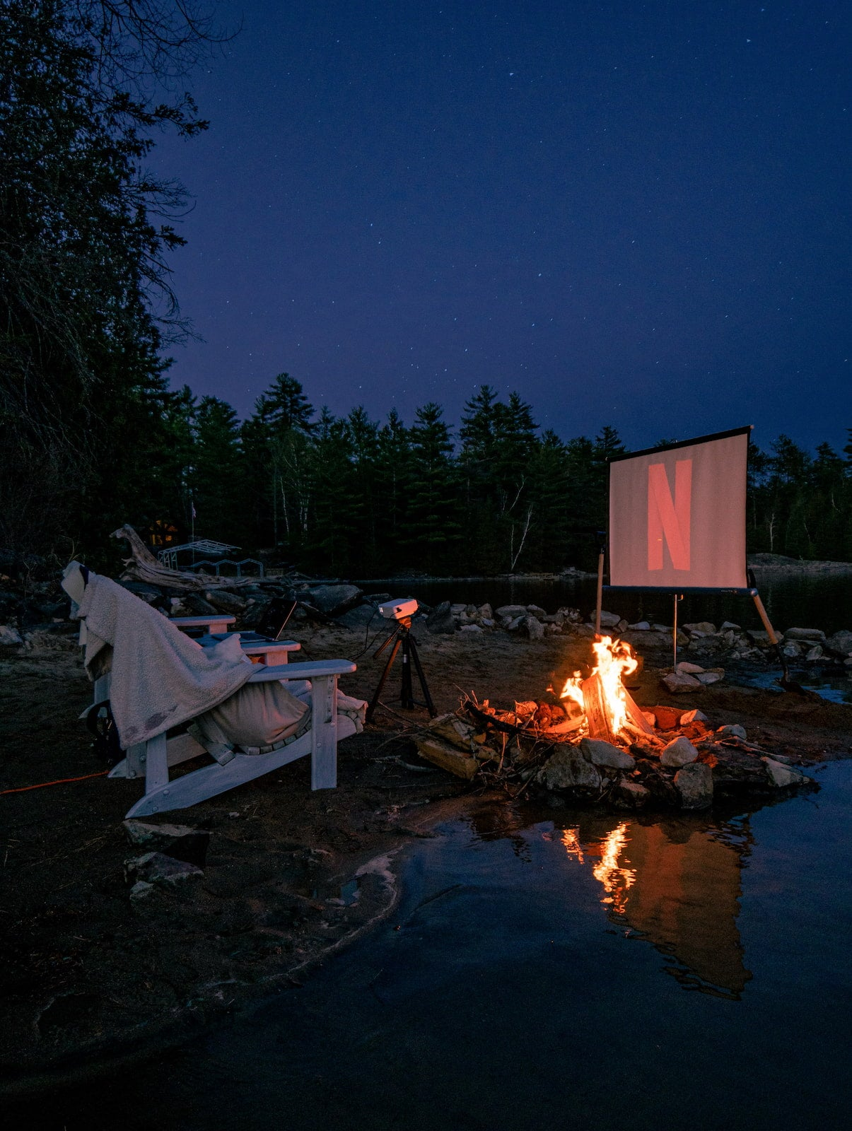 Screening a movie outside on a projector at the campsite with a campfire blazing.