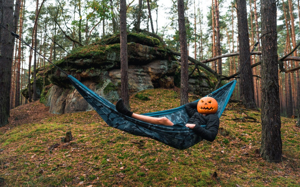 Halloween jack of lantern camper hanging out in a hammock in the woods.
