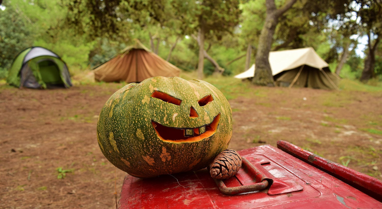 Jack o' lantern carved in front of tent at a campsite for halloween camping.